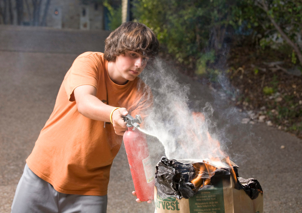 Austin, TX August 7, 2008: Fourteen-year old anglo boy attacks a small household fire with a dry chemical fire extinguisher.  Model Released.        ©Bob Daemmrich