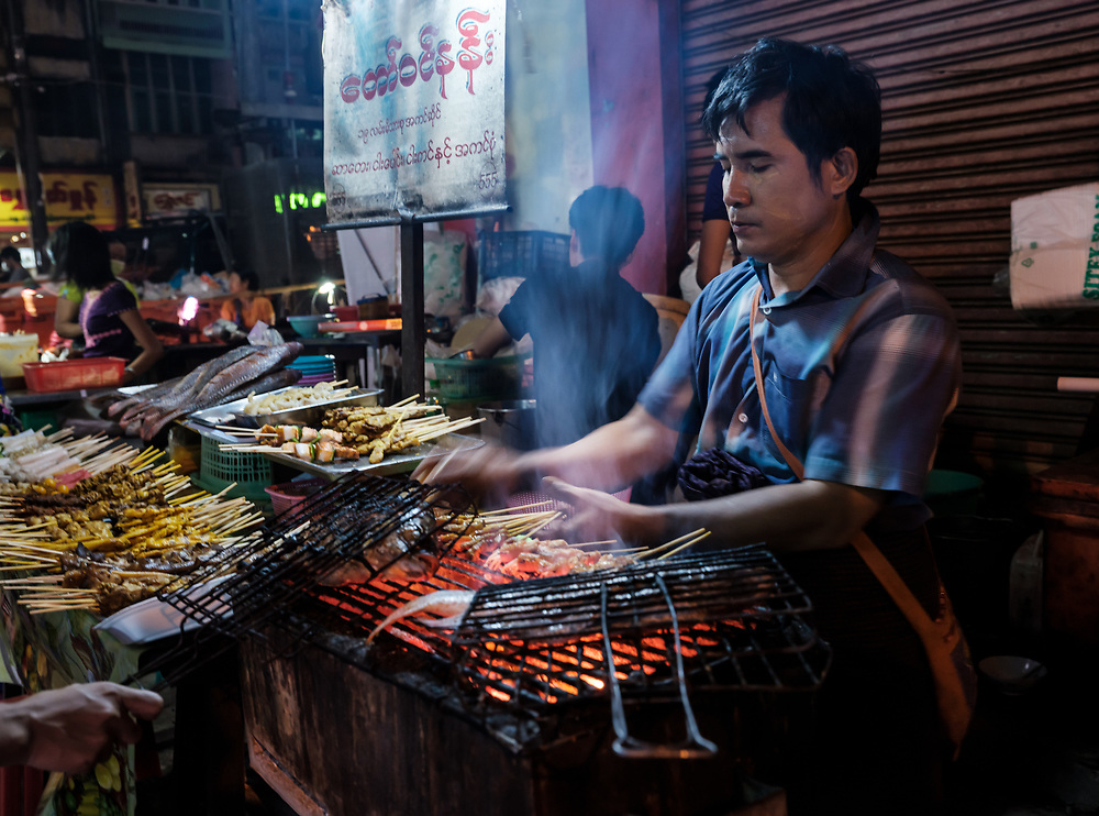 YANGON, MYANMAR - CIRCA DECEMBER 2017: Portrait of Burmese man cooking and selling food in the streets of Yangon at night.