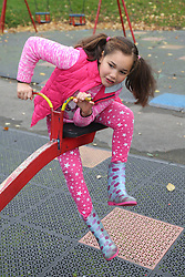 Girl on seesaw in urban park