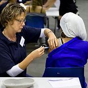 Nederland Rotterdam 30-09-2009 20090930 Foto: David Rozing ...Grootschalige vaccinatie tegen baarmoederhals kanker in Ahoy Ongeveer 5500 meisjes uit de regio Rijnmond zijn door de GGD Rotterdam uitgenodigd om zich in Ahoy preventief te laten inenten tegen baarmoederhalskanker..Het gaat om meisjes  geboren tussen 1993 en 1996 die dit voorjaar zijn gestart met de eerste prik in een serie van drie vaccinaties met hpv (humaan papillomavirus). Zij krijgen in het Rotterdamse sportpaleis hun tweede of laatste injectie.  .Vaccination for young girls, to prevent cancer of the cervix / neck of the womb. vaccine, vaccinations, vaccines, immunity, desease, deseases, preventing, prevention, shot, shots, girl, youth, ..Deze inenting zit vanaf 2009 in het Rijksvaccinatieprogramma (RVP). De GGD verzorgen de inteningen. Een volledige inenting tegen baarmoederhalskanker bestaat uit 3 prikken. De meisjes krijgen deze verdeeld over een half jaar. vaccinatie tegen baarmoederhalskanker..Inentingen in Rijksvaccinatieprogramma Vanwege de gezondheidswinst voor vrouwen is inenting tegen baarmoederhalskanker vanaf 2009 opgenomen in het RVP. Binnen het RVP krijgen meisjes de inenting steeds op de leeftijd van twaalf jaar. Baarmoederhalskanker krijg je alleen na een infectie met het humaan papillomavirus, kortweg HPV. De inenting beschermt tegen twee typen van het HPV-virus (HPV 16 en 18) die samen 70% van alle gevallen van baarmoederhalskanker veroorzaken. gezondheid, health.Holland, The Netherlands, dutch, Pays Bas, Europe ..Foto: David Rozing