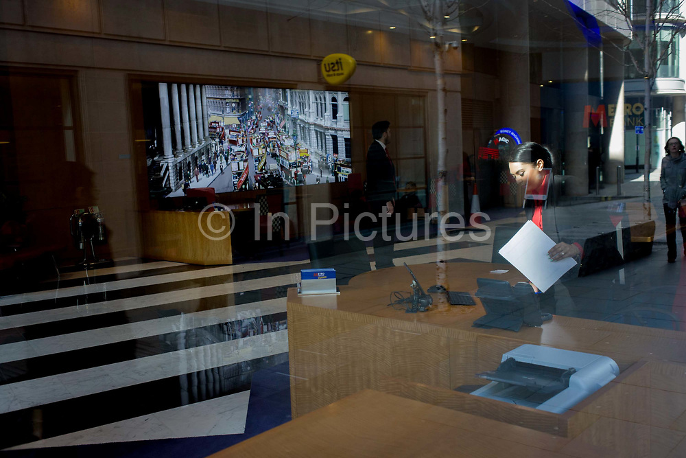 A lady Metro Bank worker and foyer featuring a vintage photo of City traffic seen through a front window. The modern-day Metro Bank offices with the backdrop of a vintage street scene, plus contemporary traffic in reflected city. Picking up her paperwork, the lady is about to temporarily leave her desk. In the background is a street scene of a bygone era, with early buses and charabancs. Incongruously the modern world is shown with today's society walking the same London streets and a ubiquitous white van. Metro Bank is Britain's first new High Street bank in over 100 years.