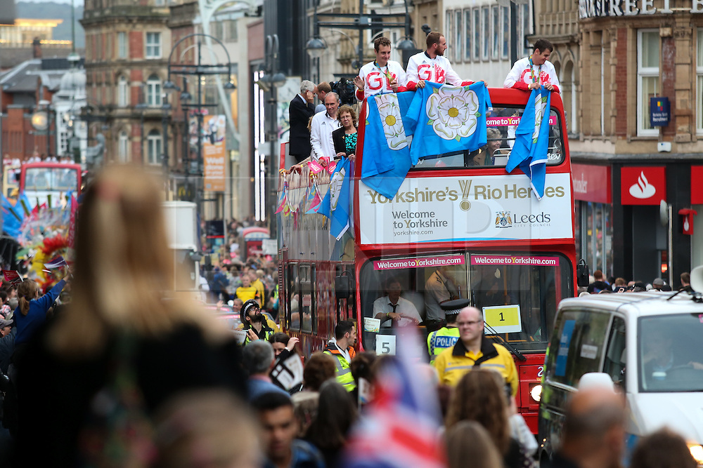 © Licensed to London News Pictures. 28/09/2016. Leeds, UK. Alistair Brownlee, Gordon Benson and Jonathan Brownlee atop an open top bus with their medals at the Olympic and Paralympic parade in Leeds. Yorkshire's Olympic and Paralympic stars receive a heroes' welcome during an open top bus parade in Leeds, West Yorkshire. . Photo credit : Ian Hinchliffe/LNP