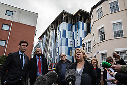 """© Licensed to London News Pictures. 16/11/2019. Bolton, UK. Mayor of Manchester ANDY BURNHAM , PAUL DENNETT of Greater Manchester's High Rise Taskforce , DAVID GREENHALGH of Bolton Council SANDRA RUIZ of Grenfell United , Deputy Mayor of Greater Manchester BEV HUGHES and TIAGO ALVES of Grenfell United at a press conference at the site of the blaze . Firefighters work at the scene where a fire broke out overnight (15th/16th November 2019) at a block of flats known as """" The Cube """" , in Bolton Town Centre . At least two people are known to have been treated by paramedics at the scene of the six-story block , which is occupied by students of the University of Bolton . Photo credit: Joel Goodman/LNP"""
