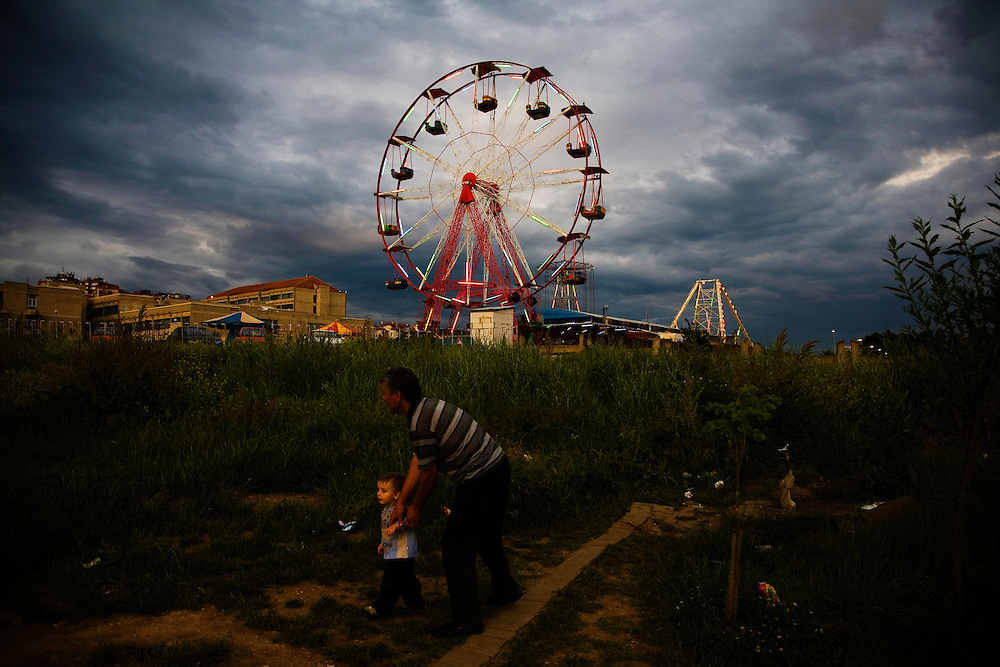 A father leads his young son through a dirty, garbage-strewn field near an amusement park in Prishtina, Kosovo.