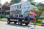 """A pickup truck with an American flag, a confederate flag, and a """"come and take it"""" flag drives through Millville, Pennsylvania on July 5, 2021 prior to the Independence Day parade."""