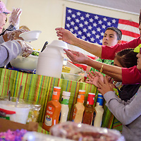 Lupe Garcia, right, helps Amber Garcia and her other grandchildren fill plates to be served to guests during the Immanuel Baptist Church Thanksgiving dinner at the Community Outreach Center in Grants Saturday.