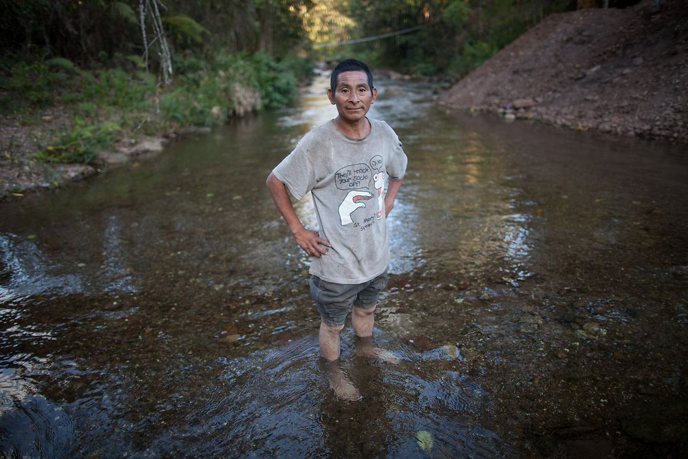 """Israel Martínez, Tolupan indigenous man from Montaña de la Flor, Honduras. """"See the frogspawn? Look, it's everywhere. See the snails in the water, on the stones? The animals drink this water, we drink this water straight from the river. The water in their [ladino] places is poisoned with fertlizers and by the ones who do the mining, they don't have frogs and snails any more, they're already dead, maybe they don't understand. They cut down their trees and now it doesn't rain any more. And now they want our land, our trees, they want to ruin our water, dry up our rivers. And they want to kill us. They are killing us""""."""