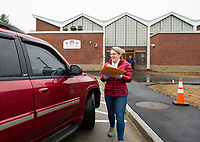 "Student Outreach Coordinator Hillary Ayers hands out student packets during the drive thru ""pick up"" at Elm Street School on Friday.  (Karen Bobotas/for the Laconia Daily Sun)"