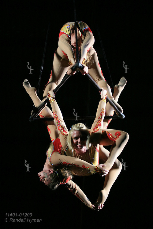 Three young women create human sculpture as they perform triangle trapeze act high above crowd at Peru Amateur Circus; Peru, Indiana.