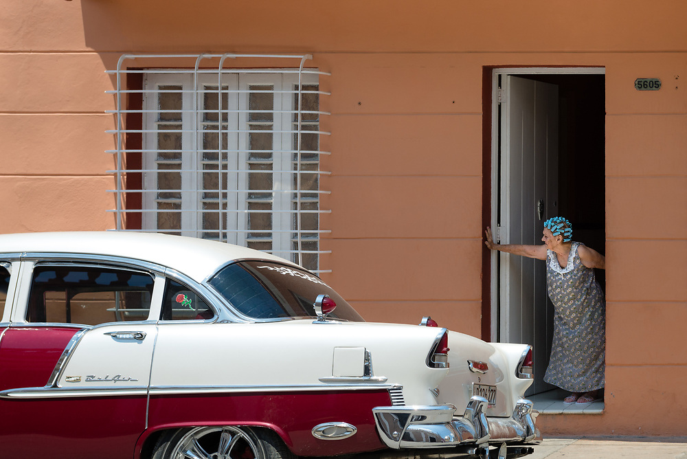 Old woman looking out of doorway with vintage car