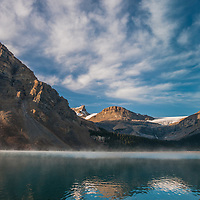 Morning mist rises over Bow Lake and the crest of the Canadian Rockies in Banff National Park, Alberta, Canada.