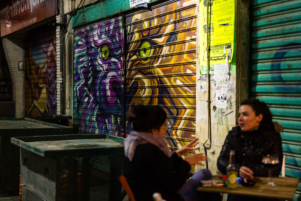 Israeli women enjoy at a local bar as they sit in front of a graffiti depicting Fanciful animals which was painted over a closed shutter at the Mahane Yehuda Market, often called 'The Shuk' in Jerusalem, Israel, on February 24, 2016.