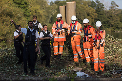 Police officers prepare to return an item taken without permission by an HS2 security guard from an anti-HS2 activist during tree felling works alongside the Grand Union Canal in connection with the HS2 high-speed rail link on 21 September 2020 in Harefield, United Kingdom.  Anti-HS2 activists continue to try to prevent or delay works for the controversial £106bn HS2 high-speed rail link on environmental and cost grounds from a series of protection camps based along the route of the line between London and Birmingham.