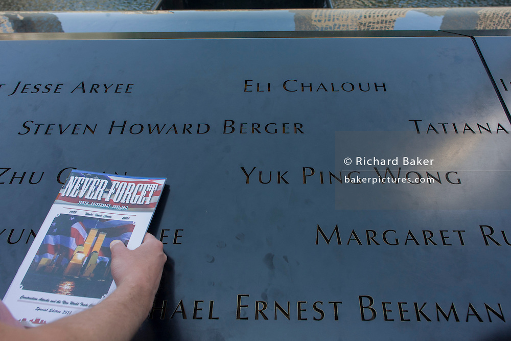 Detail of visitor's hand and names of victims at the 9/11 Memorial in New York, killed at the locations of terrorist attacks on September 11th 2001. The National September 11 Memorial is a tribute of remembrance and honor to the nearly 3,000 people killed in the terror attacks of September 11, 2001 at the World Trade Center site, near Shanksville, Pa., and at the Pentagon, as well as the six people killed in the World Trade Center bombing in February 1993.