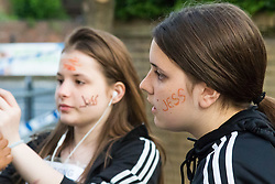 London, June 15th 2017. Local residents and well-wishers gather at a short vigil outside Notting Hill Methodist Church near the scene of the Grenfell Tower Fire Disaster in which so far seventeen people have been reported killed, with dozens injured, many still missing and scores of people rendered homeless. PICTURED: Two girls have 'JESS' written on their faces, hoping that missing twelve-year-old Jessica Urbano is found alive.