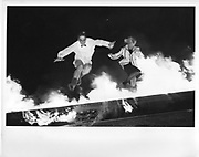 a man and woman jumping over a burning boat in cambridge 1984ONE TIME USE ONLY - DO NOT ARCHIVE  © Copyright Photograph by Dafydd Jones 66 Stockwell Park Rd. London SW9 0DA Tel 020 7733 0108 www.dafjones.com