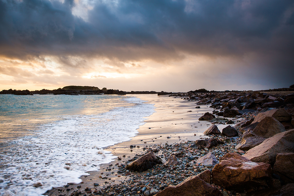 Orange glow in the sky reflecting on the sea, sand and rocks along the seashore at Green Island beach, Jersey
