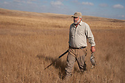 Hunter John Davidson with a grouse out on the North Dakota prairie grasslands while upland game bird hunting near Minot, North Dakota, United States. Hunters work the land to find pheasant. These men have been shooting for most of their lives and put considerable efforts into their hunting, efforts which reward them with wild game meats, none of which is wasted.