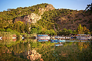 Boats on Dalyan Çayı River with Lycian Rock Tombs in the cliffs . Mediterranean coast Turkey.<br /> <br /> If you prefer to buy from our ALAMY PHOTO LIBRARY  Collection visit : https://www.alamy.com/portfolio/paul-williams-funkystock/dalyan-lycian-tombs-and-kaunos.html<br /> <br /> Visit our TURKEY PHOTO COLLECTIONS for more photos to download or buy as wall art prints https://funkystock.photoshelter.com/gallery-collection/3f-Pictures-of-Turkey-Turkey-Photos-Images-Fotos/C0000U.hJWkZxAbg