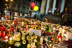 "© Licensed to London News Pictures. 23/03/2016. Brussels, Belgium. Late night vigil one day after the attacks - Place de la Bourse, a large crowd gather to light candles, sing and write messages in chalk on the paving stones of the square.  A group stand off to one side with placards reading ""We are together against terrorism""and ""Counter terrorism and hate"" and are embraced by a passer by. Photo credit: Guilhem Baker/LNP"