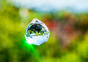 Jewel Crystal hanging outdoors with a defocused natural green background