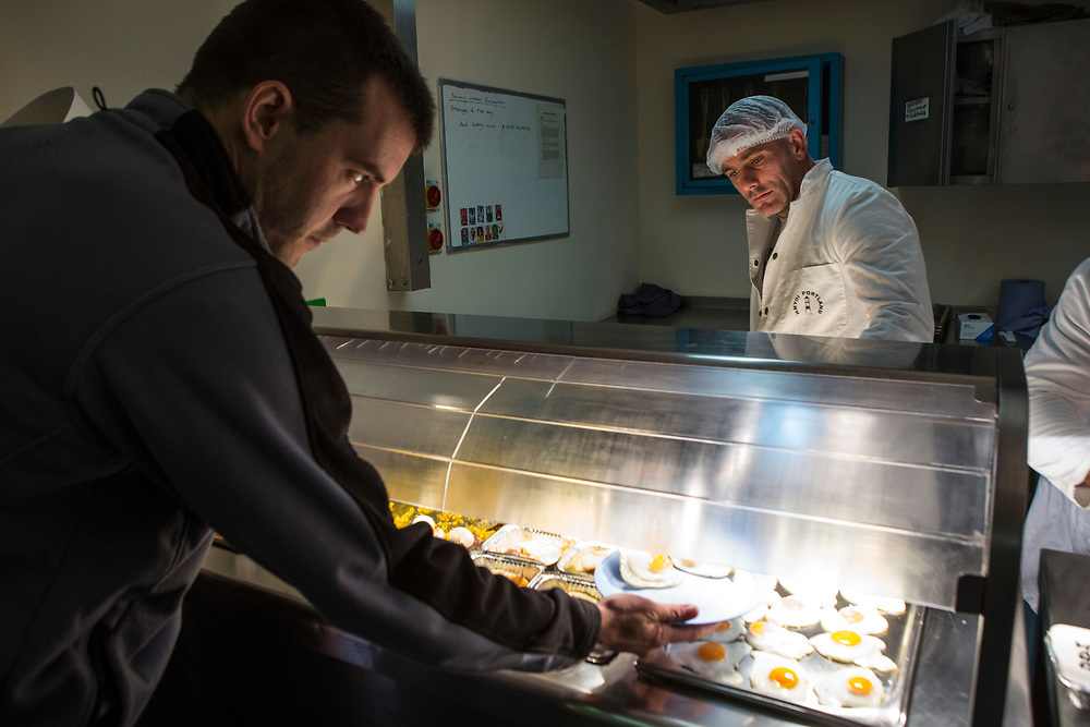 Prisoners working in the wing servery. All meals are served to prisoners from the service hatch, food is collected and they return to their cells to eat. HMP/YOI Portland, Dorset, United Kingdom.