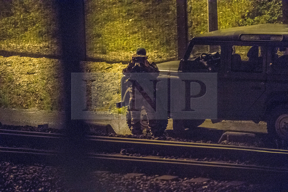 © London News Pictures. Calais, France. A member of the French military using night vision to watch the tracks at the entrance to the Eurotunnel. Migrants attempting to reach the UK via the Eurotunnel at Calais in France. The situation has reached crisis point, which French police over run by attempts to cross the border. Photo credit: Ben Cawthra /LNP