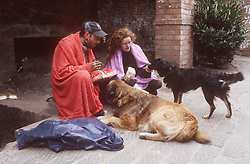 Homeless couple sitting in street wrapped in blankets feeding pet dogs,