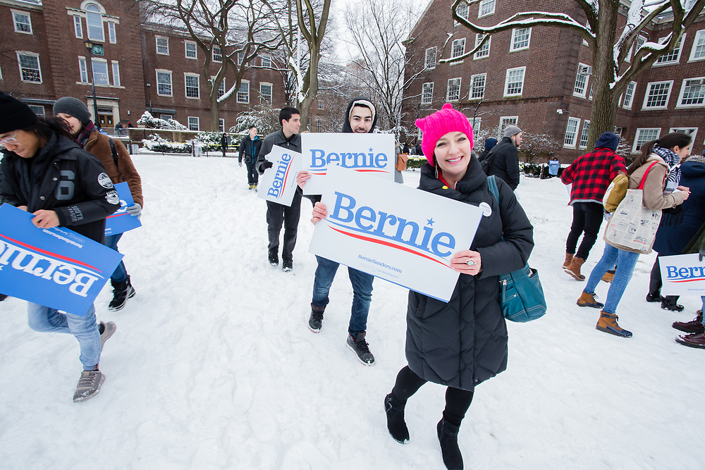 Brooklyn, NY - 2 March 2019. A woman coming in to Bernie Sanders' first rally for the 2020 presidential primary at Brooklyn College ears a pink pussy hat and carries  Bernie sign.