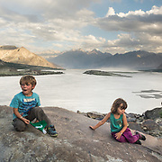 Young boy and girl sit on a rock next to a large mountain lake.