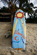 """SHOT 1/18/2007- A surfboard advertises a seafood restaurant along the beach in Sayulita, Mexico. Sayulita is a small fishing village about 25 miles north of downtown Puerto Vallarta in the state of Nayarit, Mexico. Known for its rivermouth surfbreak, roving surfers """"discovered"""" Sayulita in the late 60's with the construction of Mexican Highway 200. Today, Sayulita is a prosperous growing village of approximately 4,000 residents. Hailed as a popular off-the-beaten-path travel destination, Sayulita offers a variety of activities such as horseback riding, hiking, jungle canopy tours, snorkeling and fishing. Still a mecca for beginner surfers of all ages, the quaint town attracts upscale tourists with its numerous art galleries and restaurants as well. Sayulita has a curious eclectic quality, frequented by native Cora and Huichol peoples, travelling craftsmen (and women) as well as by international tourists. Sayulita is the crown jewel in the newly designated """"Riviera Nayarit"""", the coastal corridor from Litibu to San Blas. It's stunning natural beauty and easy access to Puerto Vallarta have made Sayulita real estate some of the most sought after in all of Mexico..(Photo by Marc Piscotty © 2007)"""