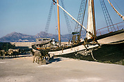 Wooden sailing ship cargo vessel loaded with mules at harbour of port, Calvi, Corsica, France in late 1950s