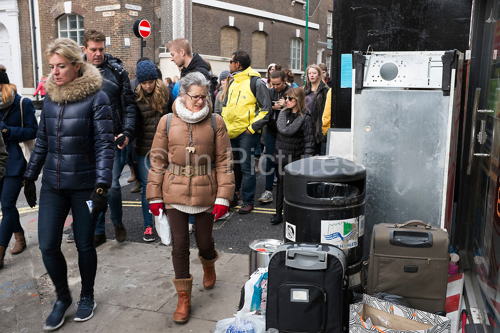 Street scene at Brick Lane Market in the East End of London, UK. A tour group looks and grimaces at waste left by a rubbish bin. This area is known for it's eclectic, brilliant, sometimes bizarre fashion as young people meet up on Sunday, market day, and time for people to gather, hang out, and maybe find a bargain.