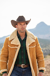 hot cowboy in a sheepskin jacket on a mountain range