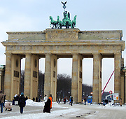 Brandenburg Gate, Berlin. This is a former city gate, rebuilt in the late 18th century as a neoclassical triumphal arch and one of the most well-known landmarks of Germany. It is located west of the city centre. One block to the north stands the Reichstag building. Having suffered considerable damage in World War II, the Brandenburg Gate was fully restored from 2000 to 2002. During the post-war partition of Germany, the gate was isolated and inaccessible immediately next to the Berlin Wall and the area around the gate featured most prominently in the media coverage of the opening of the wall in 1989.The famous statue on top of the gate is Victoria, the goddess of triumph riding atop a four horsed chariot. It was crafted by the sculptor Gottfried Schadow.