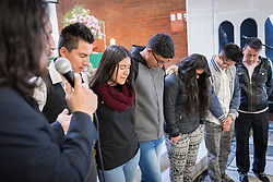 18 November 2018, Bogotá, Colombia: Rev. John Rojas blesses a group of recent graduates from the church-run school. The church of San Lucas ('Saint Lucas') of the Evangelical Lutheran Church of Colombia, brings together a congregation of some 100 people in the southern areas of Bogotá. Located in the Kennedy area, the church has recently celebrated 50 years. As part of its ministry, the church runs a school and college, The Colegio Evangelico Luterano de Colombia (CELCO) San Lucas, offering education to just over 1,000 students aged 3-18. The school started as a social initiative offering care for children aged 0-4 in Bogotá's less wealthy neighbourhood, allowing the parents opportunities to go to work. 36 years after its foundation, the school employs 56 staff, of which 36 are teachers.