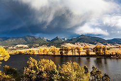Fall colors, rainbow and thunderstorm in Paradise Valley. Golden Cottonwoods and aspen line the banks of the Yellowstone River as a thunderstorm pelts the Absaroka Mountains in the distance.