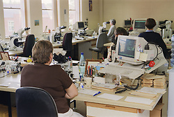 Biomedical scientists in cytology laboratory using microscopes to screen cervical smears,