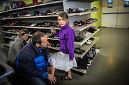 """Julia Bacher and Clifford Lubilz help their daughter Jailyn Lubilz, 7, try on shoes at the Goodwill store in Burlington, Vermont on April 20, 2013.  A young family on a budget, they're conscious of where their money goes. """"She just burns through shoes,"""" Clifford said. """"Every so often we do a complete overhaul. This is a good place to do it.""""<br /> (photo by Jenna Isaacson Pfueller)"""