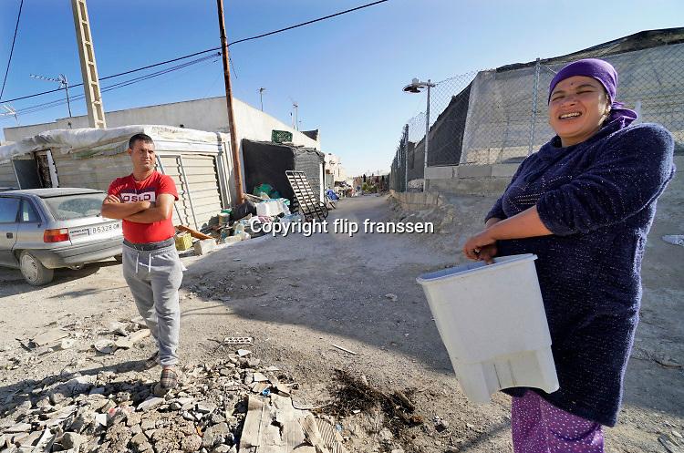 Spanje, El Ejido, 8-11-2019 Een Marokkaans echtpaar  woont in een klein huisje, voorheen boeren arbeiderswoningen tussen de plastic kassen.  In dit deel van Andalucie worden veel groenten en fruit verbouwd die hun weg vinden via de export naar o.a. Nederland . Het wordt de zee van plastic genoemd omdat de kassen opgebouwd zijn van houten of metalen palen bedekt met zwaar plastic. In de kassen werken voornamelijk migranten uit Afrika, en arbeidsmigranten uit Oost-Europa die een laag loon uitbetaald krijgen, tussen de 30 en 40 euro per 8 urige dag, werkdag, afhankelijk van de werkgever.Foto: Flip Franssen
