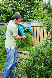 Emptying grass clippings onto the compost heap