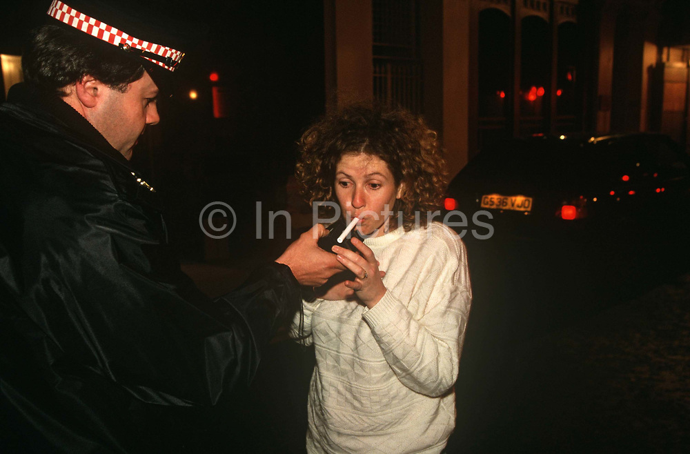 A woman driver is breathalysed at the roadside by an officer from the City of London Police. During a night shift in the streets near Liverpool Street Station, the lady blows into the device until the officer tells her to stop, having supplied sufficient breath that can be measured for alcohol in milligrams of Oxygen. When the user exhales into the breathalyzer, any ethanol present in their breath is oxidized to acetic acid at the anode. The overall reaction is the oxidation of ethanol to acetic acid and water. The electrical current produced by this reaction is measured, processed, and displayed as an approximation of overall blood alcohol content by the breathalyser. The first practical roadside breath-testing device intended for use by the police was the drunkometer. The drunkometer was developed by Professor Harger in 1938.