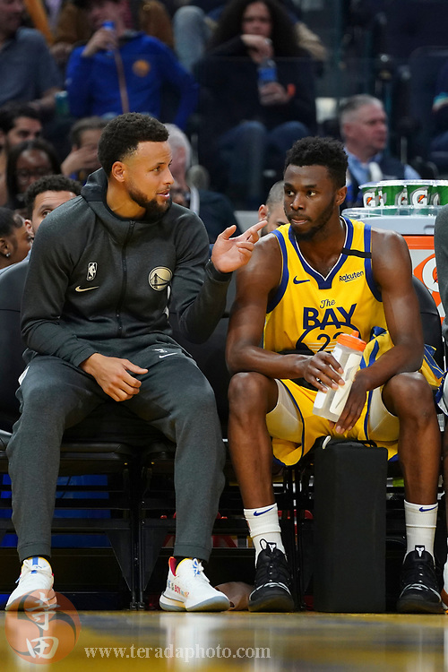 February 23, 2020; San Francisco, California, USA; Golden State Warriors guard Stephen Curry (30, left) talks to guard Andrew Wiggins (22, right) during the third quarter against the New Orleans Pelicans at Chase Center.