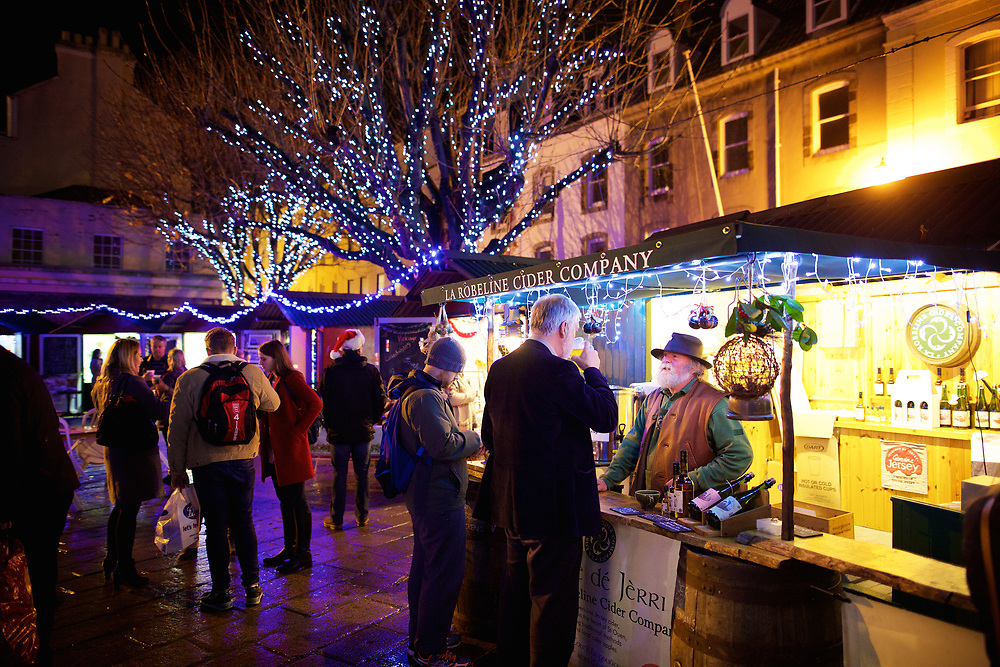 People tasting the local cider and shopping at the market stalls in the Royal Square, St Helier Jersey, which are lit up by the Christmas lights in the trees