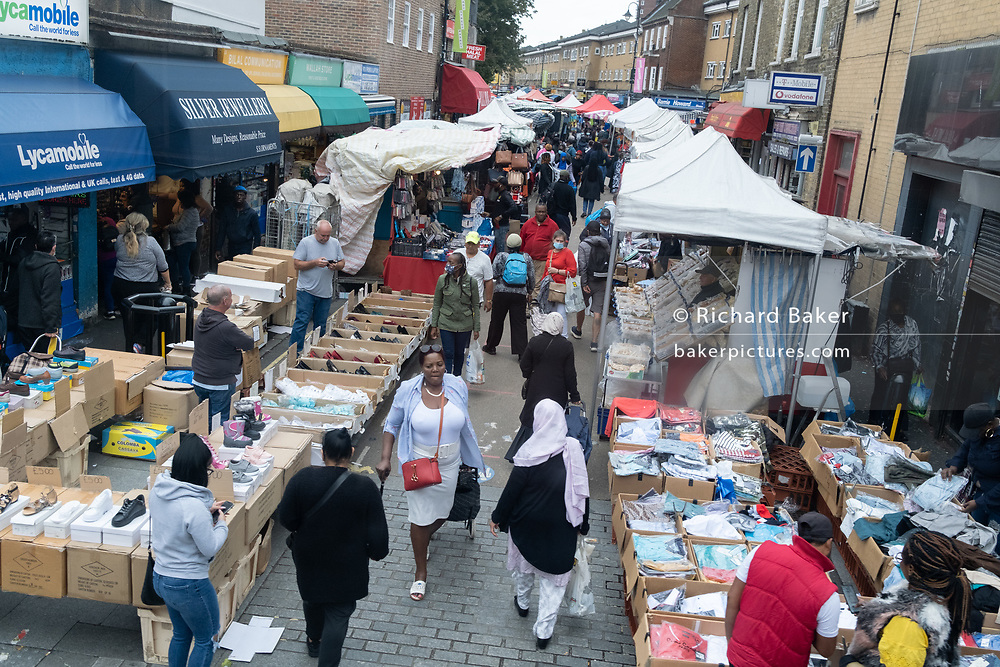 Saturday afternoon shoppers buy goods and produce from the stallholders of East Street Market on the Walworth Road in Southwark, on 29th August 2020, in London, England,