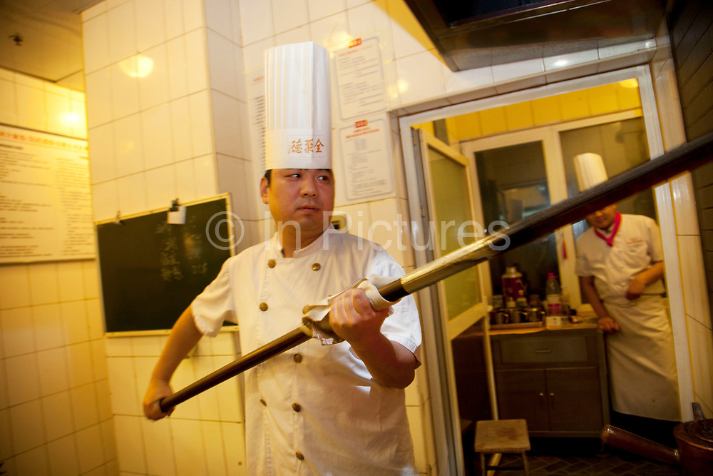 Behind the scenes in the kitchen where the ducks are roasted in wood burning ovens, a chef performs his work duties turning and removing cooked ducks. Quanjude roast duck restaurant in Wangfujing, Beijing. This is a Chinese restaurant known for its trademark Peking Roast Duck and is known for being the best roast duck restaurant in China. Quanjude was established in 1864 during the Qing Dynasty under the reign of the Tongzhi Emperor. Although Peking Duck can trace its history many centuries back, Quanjude's heritage of roast duck preparation - using open ovens and non-smoky hardwood fuel such as Chinese date, peach, or pear to add a subtle fruity flavor with a golden crisp to the skin, was originally reserved for the imperial families.