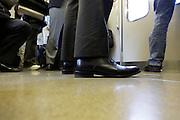 low angle view of office worker standing in commuter train