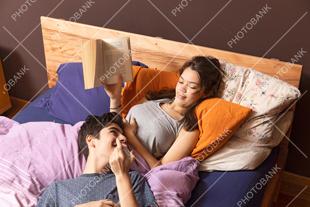 Young couple is lying in bed. They both look at the phone while they have fun