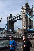 People jogging past Tower Bridge.