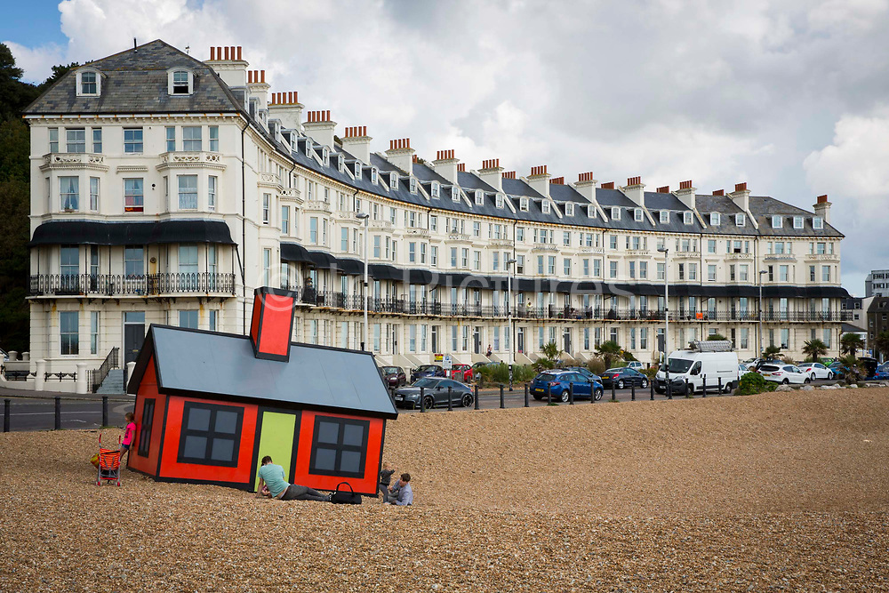 Holiday home. A red bungalow on Folkestone beach front built by the artist Richard Woods as part of the 2017 Folkestone Triennial. Folkestone, Kent. The artist wanted to create a piece about second homes and the housing crisis in the UK.
